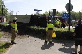 Vrachtwagen met tuinafval kantelt op N264, chauffeur knel in cabine